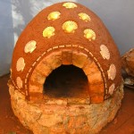 Cooking in finished earth clay cob bread and pizza oven.