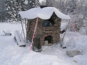 Winter snow around and on top of oven.