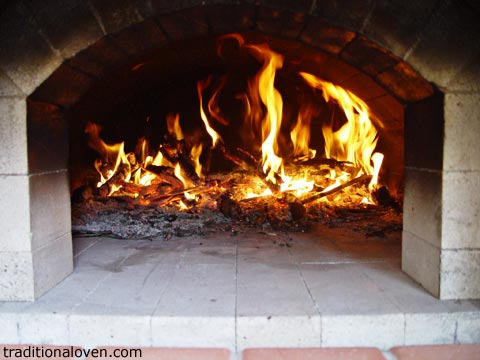 Photo of brick oven dome being heated up by wood fire.