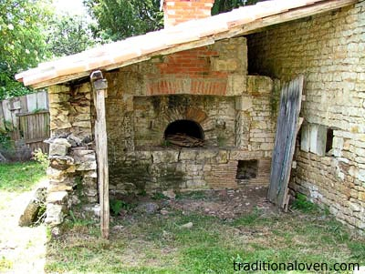 Picture of a stone wall house and wood oven built in 1930 in France.
