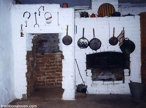 Photograph of fireplace and wood firing oven in an old cottage kitchen.