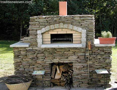 Backyard garden pizza oven built of stones on outside.