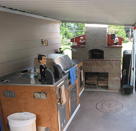 Home outdoor kitchen with brick pizza oven.