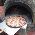 Pizza cooked in round Sursur igloo shaped oven.