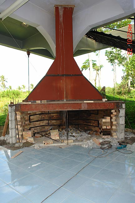 Brick oven with fireplace both having water pipes heat exchanger installed around its dense dome