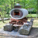 Pizza oven built in elliptical concrete drainage pipe.