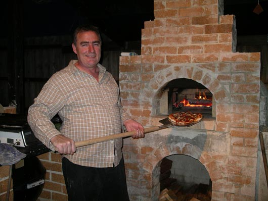 Making Pizzas In Outdoors Pizza Oven.