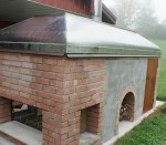 fireplace with oven and metal hood cover