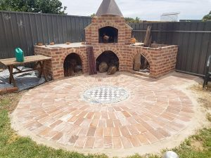 A round ground mosaic from bricks and tiles with fireplace plus oven.