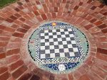 Circular ground mosaic of tiles and bricks.